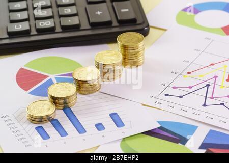 Pilas de monedas de oro están en cartas de colores. Análisis del estado de los negocios