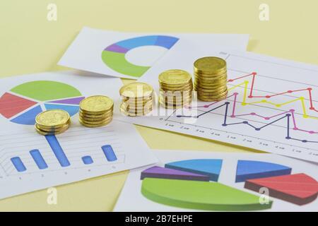 Aumento en tamaño pilas de monedas de oro y gráficos de color sobre un fondo amarillo. Preparación del informe a los inversores sobre la situación financiera