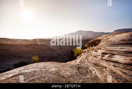 Cañón volcánico con capas en el desierto con montañas en el hermoso atardecer