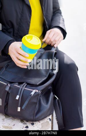 Taza de café reutilizable con las manos femeninas. Llévate el café a cualquier parte con una taza reutilizable.