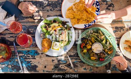 Vista plana de almuerzo vegetariano servido al aire libre en una mesa de comedor rústica