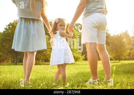 Feliz familia caminando en la hierba en el parque de verano. Día De La Protección De Los Niños. Foto de stock