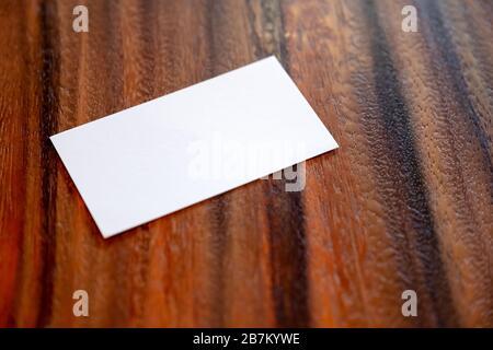 Una tarjeta de visita blanca en blanco sobre fondo de madera vintage