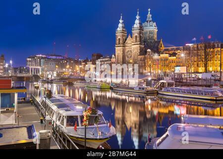 Amsterdam, países Bajos escena del canal por la noche con la Basílica de San Nicolás y los barcos fluviales.