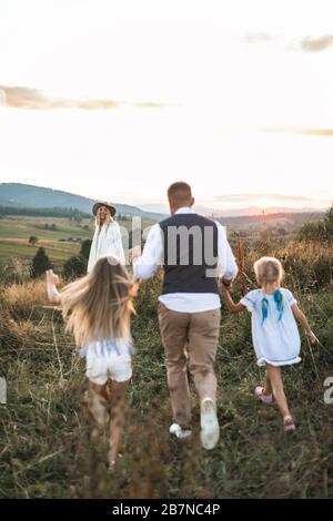 Familia Stylilsh, padre, madre y dos pequeñas hijas lindas divertirse y correr en el campo salvaje de verano.