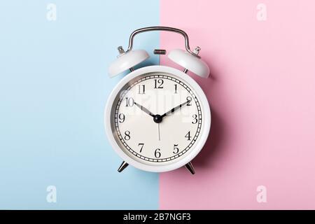 Reloj despertador blanco vintage sobre fondo azul y rosa. Concepto de tiempo