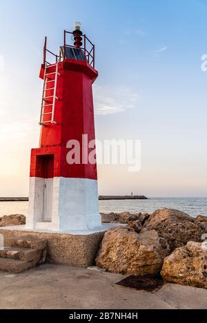 Disparo vertical de un faro cerca del mar bajo un cielo azul Foto de stock