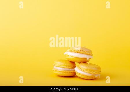 Tres macarrones de limón amarillo en pila sobre fondo amarillo, primer plano, lugar para texto, espacio de copia, horizontal