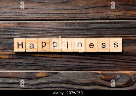 Palabra de felicidad escrita en bloque de madera. Texto de felicidad sobre mesa de madera para su diseño, concepto de vista superior.