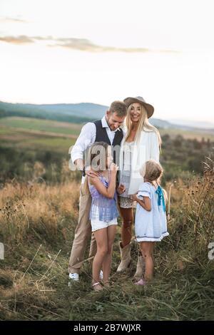 Feliz y sonriente familia joven, padre, madre y dos hijas pequeñas que se divierten al aire libre, de pie juntos en un campo salvaje. Mamá y papá hablando con