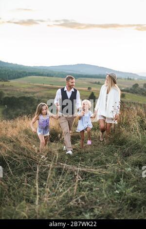 Feliz familia, joven padre, madre con sus hijos hijas caminando en el campo al atardecer en una cálida noche de verano. Relájese en el campo