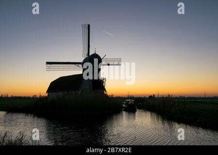 Vista panorámica de la silueta de un molino holandés contra el cielo crepúsculo