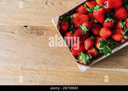 Una caja de fruta llena de fresas vista desde arriba sobre una mesa de madera