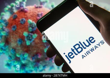 En esta ilustración de la foto se muestra el logotipo de la aerolínea estadounidense de bajo coste JetBlue Airways en un smartphone con un modelo de ordenador del coronavirus COVID-19 en el fondo.