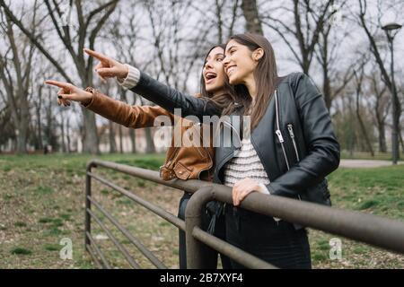 Las niñas apuntando con el dedo lejos en el parque