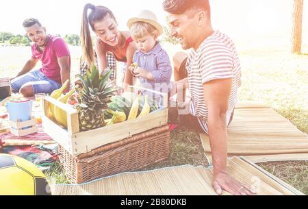 Familias felices haciendo picnic en el parque natural al aire libre - padres jóvenes divertirse con los niños en verano comiendo fruta fresca y riendo juntos - Amor Foto de stock