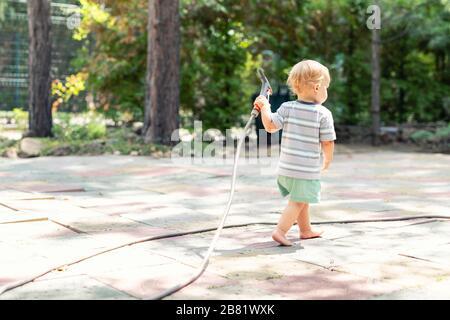 Cute adorable rubia caucásica barefeet muchacho caminando en casa patio tubo sujetando la manguera para regar el jardín. Niño pequeño ayudante jugando en jardinería