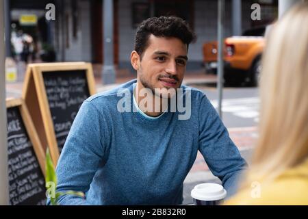 Pareja caucásica en la ciudad sentada en una terraza de café