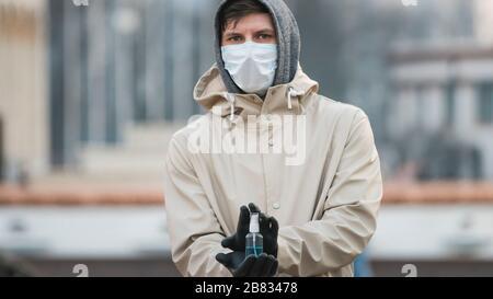 Primer plano de la persona joven sosteniendo en la mano un antiséptico o un aerosol anti-bacterias. Desinfección de las manos. Concepto de atención de salud durante una epidemia o pande