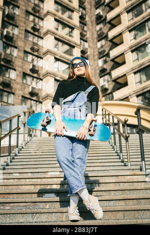 Joven mujer caucásica posando en la calle con monopatín en las manos. Niña adolescente en jeans azules deportes extremos en un ambiente urbano. Tema de la juventud