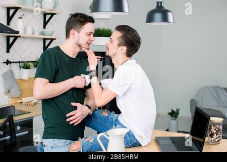 Jóvenes amantes homosexuales mirarse unos a otros en casa. Feliz y sonriente pareja gay bebiendo café juntos en la cocina.