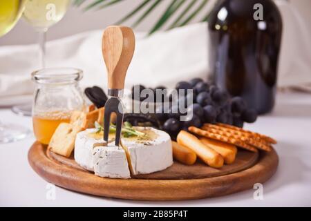 botella de vino tinto y plato con queso variado, fruta y otros aperitivos para fiestas