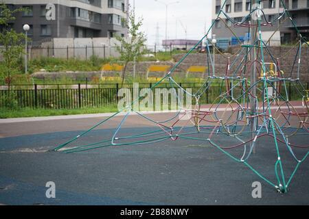 Vaciar el equipo de cuerda en el patio de juegos de verano de los niños en la ciudad sin nadie