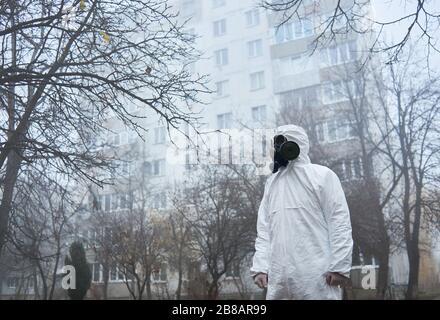 Vista lateral del ecólogo en uniforme protector de pie en calle foggy y mirando a un lado. Hombre ambientalista con traje blanco y máscara de gas. Concepto de ecología y contaminación ambiental.