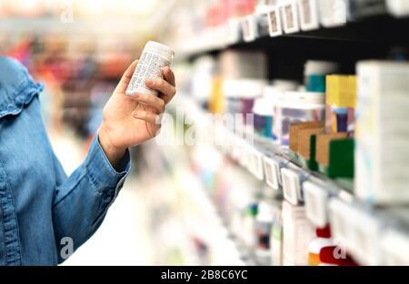 Cliente en farmacia sosteniendo botella de medicamento. Mujer leyendo el texto de la etiqueta acerca de la información médica o los efectos secundarios en la farmacia. Compras de pacientes.