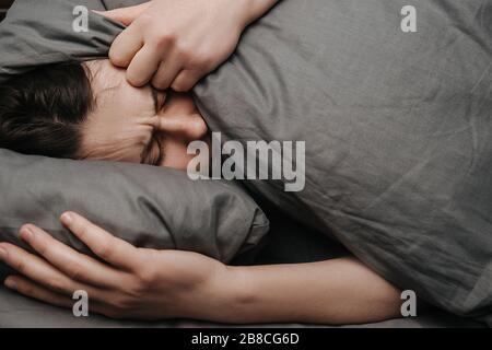 Triste mujer joven deprimida acostada en la cama que cubre la cabeza con la almohada se siente infeliz y solo, chica infeliz engorada sufre de daño de ruptura Foto de stock