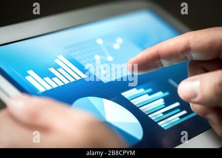 Estadísticas, gráficos, tendencias y crecimiento en la pantalla de la tableta. Gestión financiera y desarrollo con tecnología en los negocios. Businessman con monitor. Foto de stock
