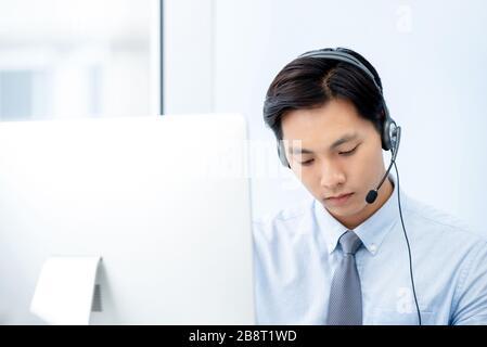 El atractivo personal de telemarketing asiático lleva puesto unos auriculares que se centran en trabajar en la oficina