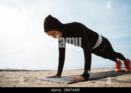 ajuste mujer musulmana haciendo empuje hacia arriba al aire libre. deporte mujer entrenamiento