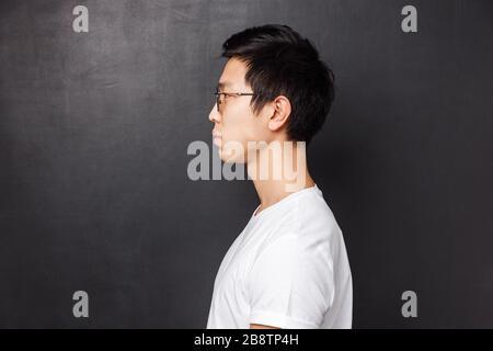 Retrato de perfil de un joven asiático adulto de aspecto serio en una camiseta y unas gafas blancas, centrado en el lado izquierdo del espacio para copias, de pie