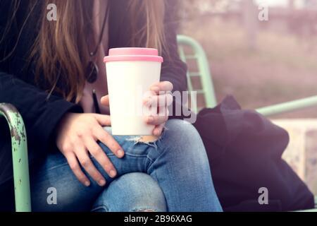 Taza de café reutilizable con manos femeninas. Concepto de estilo de vida sostenible.
