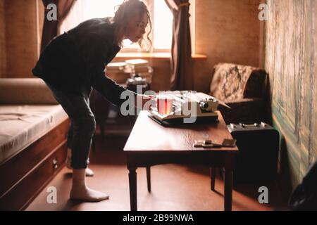 Mujer joven sosteniendo una taza de té de pie en la sala de estar en casa Foto de stock