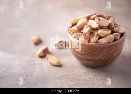 Nueces de Brasil en cuenco de madera sobre fondo texturizado de madera. Espacio de copia. Superfood, vegan, comida vegetariana concepto. Macro de la textura de la nuez de brasil, selectiva