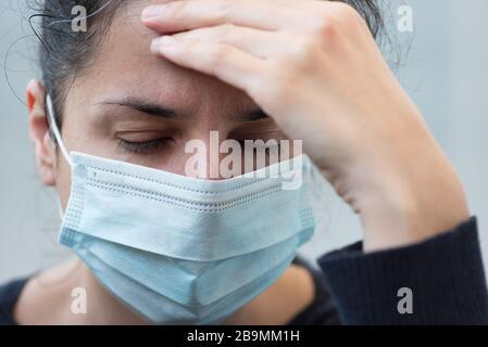 Mujer de cerca que lleva una máscara quirúrgica de cara que sostiene su cabeza y que tiene dolor de cabeza sobre fondo gris. Enfoque selectivo. Gripe, enfermedad, concepto pandémico