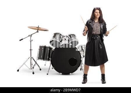 Retrato completo de una joven baterista con palillos de batería con un juego de batería aislado sobre fondo blanco