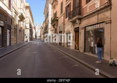 ROMA, ITALIA - 12 de marzo de 2020: Una mujer se encuentra frente a las tiendas cerradas de Via dei Condotti, junto a la Plaza de España, Roma, Italia. Uno debe justificar el