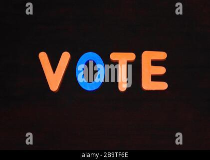 Vote la palabra escrita con diferentes bloques de letras de colores dispuestos sobre un fondo oscuro