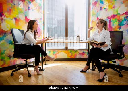 Compañeros de trabajo en la reunión de la oficina en espacios de trabajo coloridos innovando, colaborando, diseñando, branding, diseñadores artísticos