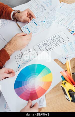 Vista recortada de los diseñadores que trabajan con plantillas de diseño ux y círculo de color en la tabla