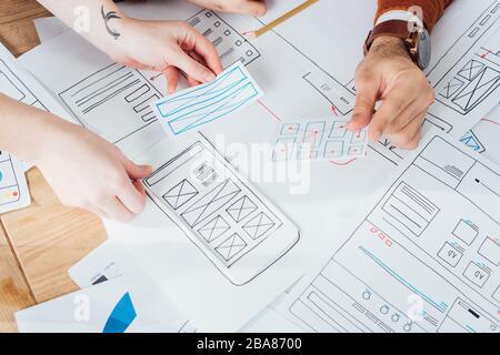 Vista recortada de la interfaz de planificación de diseñadores ux de sitio web móvil con diseños en la tabla