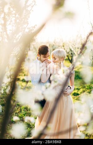 Feliz pareja romántica agradable en el hermoso jardín floreciente, disfrutando de la caminata. El hombre besando la mano de su bonita mujer. Vista a través de la floración