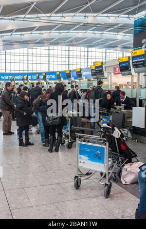 Terminal Five, aeropuerto de Heathrow, Londres. Los pasajeros esperan en cola, haciendo cola en los mostradores de facturación de equipajes.