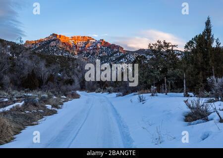 En el desierto del sur de Utah en febrero, la nieve cubre un pequeño sendero hacia el desierto. En lo alto, un gran acantilado de arenisca naranja está iluminado por el