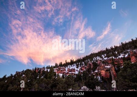 En un cañón remoto del desierto de Utah, los acantilados rojos están cubiertos de nieve en invierno. Arriba las nubes de whisky están iluminadas en rosa durante la puesta de sol.