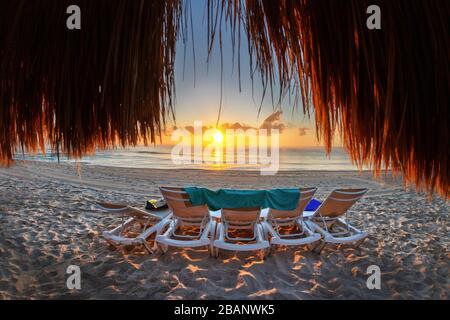 Hermoso amanecer dorado sobre una playa vacía y una fila de tumbonas en la costa caribeña de México en Riviera Maya en Cancún visto desde atrás