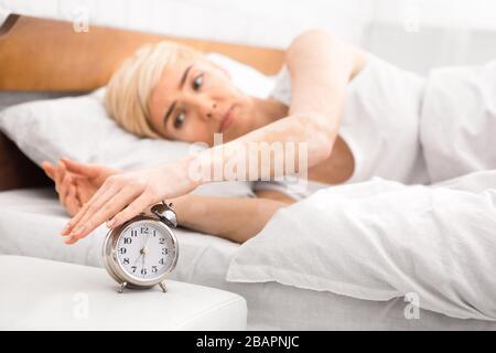 Mujer despertando y apagando el despertador